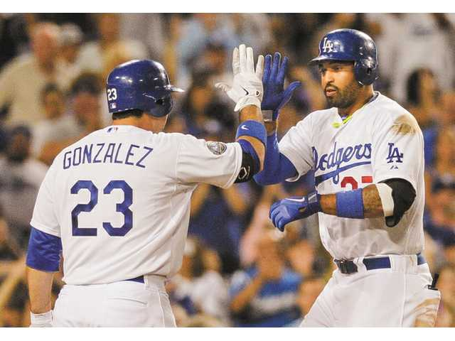 Los Angeles Dodger Adrian Gonzalez (23) congratulates Matt Kemp after he hits a solo home run on Saturday night at Dodger Stadium.