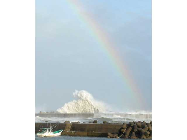 A rainbow appears while high waves hit a breakwater in Kihocho, Mie prefecture, western Japan on Sunday.