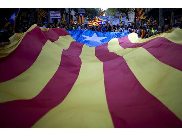 In this 2012 file photo, demonstrators carry a huge Catalan flag during a protest rally demanding independence for Catalonia in Barcelona, Spain.