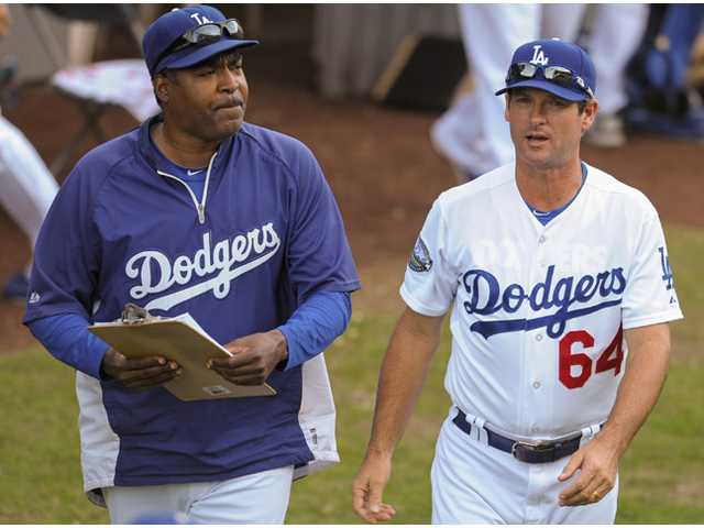 One of the Los Angeles Dodgers' pitching coaches, Chuck Crim, right, walks next to bullpen coach Ken Howell on Sunday in Los Angeles.