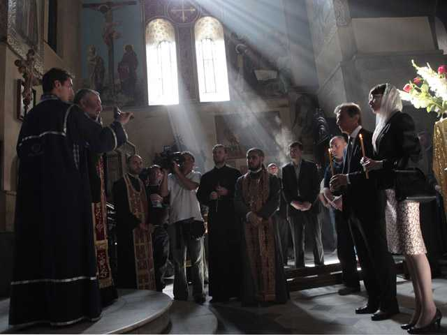 Georgia's billionaire and opposition leader Bidzina Ivanishvili, second right, and his wife, right, pray in a church in Tbilisi, Georgia.