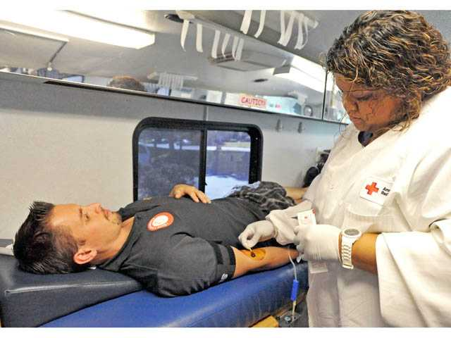 Phlebotomy technician Helen Simon performs an iodine prep on Luis De Armero, of Valencia, as he donates blood in Valencia on Monday