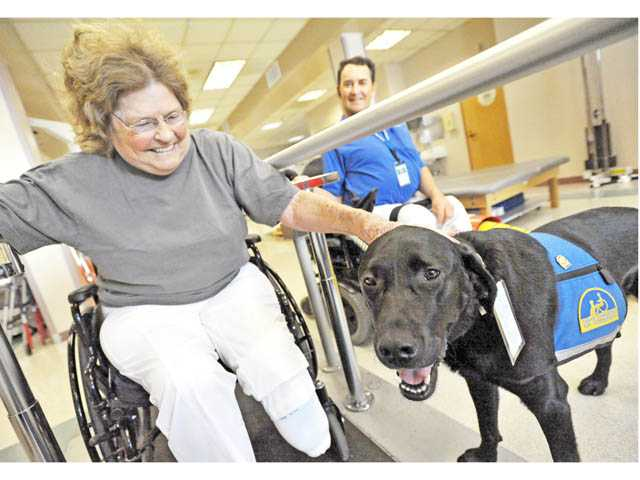 Barbara Moss of Valencia spends a moment with Logan, in the hospital's therapy gym. (Jonathan Pobre/The Signal)