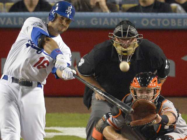 Los Angeles Dodgers' Andre Ethier, left, hits a two-run home run as San Francisco Giants catcher Buster Posey, right, catches and home plate umpire Jerry Layne watches during the fourth inning of their baseball game, on Monday in Los Angeles.