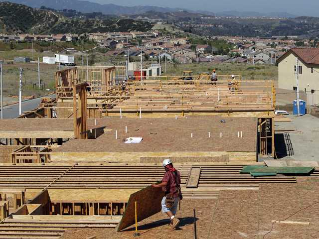 In this Wednesday, May 16, 2012, photo, construction workers work on a new house in the Crestview area in Santa Clarita, Calif. U.S. builders started work on more single-family homes in May and requested the most permits to build homes and apartments in three and a half years. The increase suggests the housing market is slowly recovering even as other areas of the economy have weakened.
