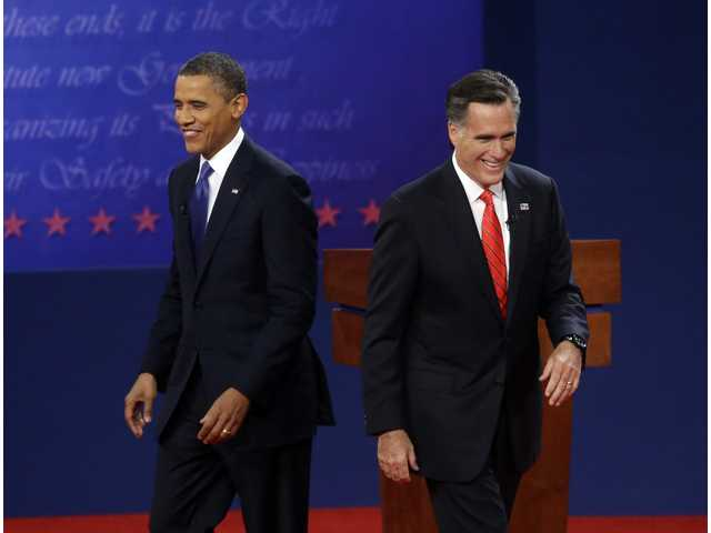 Republican presidential candidate, former Massachusetts Gov. Mitt Romney, right, and President Barack Obama, left, walk on stage at the end of their first debate at the University of Denver on Wednesday in Denver.