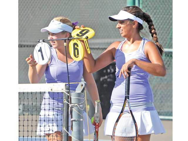 Valencia doubles team Lindsay Wolf, left, and Alekhya Bommireddipalli adjust the score during a match against West Ranch at Valencia High on Wednesday.