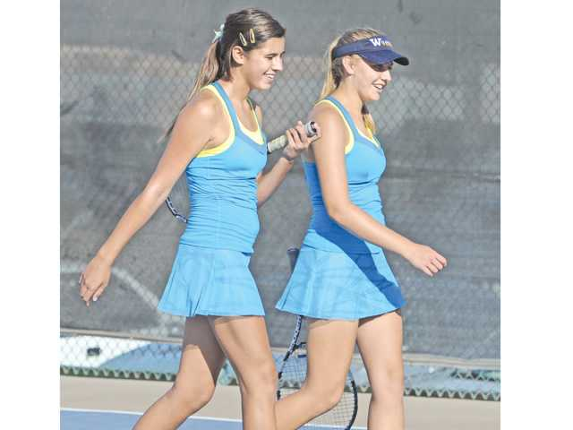 The West Ranch doubles team of MacKenzie Lyle, left, and Amanda Wilkinson celebrate thier set victory in a match against Valencia at Valencia High on Wednesday.