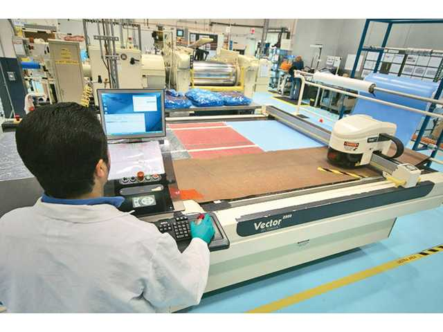 An operator is using automated cutting equipment to prepare uncured elastomer cushion for molding at TA Aerospace in Valencia.