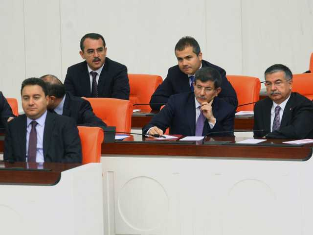 Deputy Turkish Prime Minister Ali Babacan, left, Foreign Minister Ahmet Davutoglu, second right, and other ministers listen during a debate at Turkey's parliament.