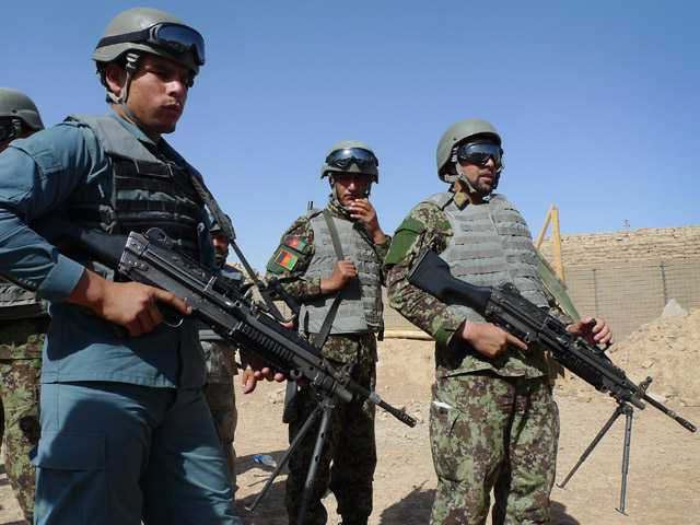In this June 19 photo, Afghan soldiers and a policeman prepare for a training exercise at the U.S. Marine-run Joint Sustainment Academy, Camp Leatherneck in Helmand.