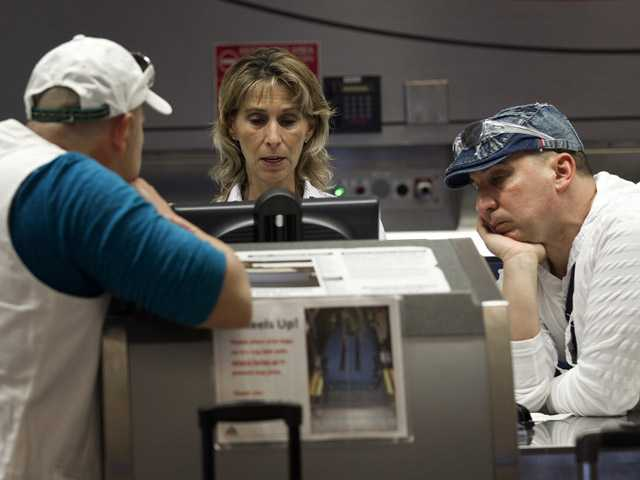 Two unidentified American Airlines passengers talk to a customer service representative, center, Friday in Miami.