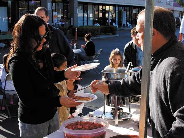 A  volunteer serves pancakes and bacon at the 2009 pancake breakfast event held by North Park Church. (Martha Garcia/The Signal)