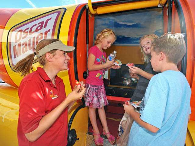 """From left, brand ambassador """"Cookout Kelly"""" Goldthorpe introduces the Oscar Mayer Wienermobile to siblings Avery, 7, Nolan, 8, and Evan Swailes, 7, of Saugus outside the Albertsons in Saugus on Wednesday."""