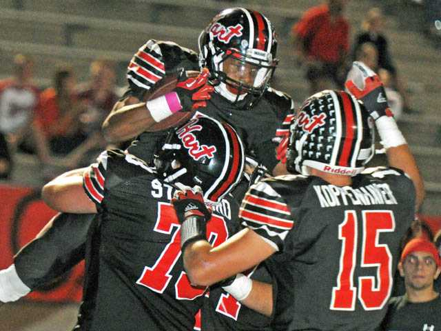 Hart running back Antoine Holmes is congratulated by teammates Erik Stafford (73) and Davis Koppenhaver (15) after he scores a touchdown against West Ranch on Friday night at College of the Canyons