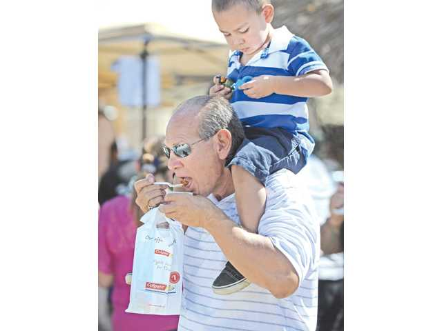 Louie Barragan samples chili while Yogi Barragan, 2, sits on his shoulders at the LASD Fun In The Sun Chili Cook off in Castaic on Saturday.