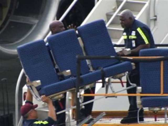 """Seats from an American Airlines 757 are carried before receiving """"Main Cabin Extra Refurbishment"""" Tuesday at Logan International Airport in Boston."""