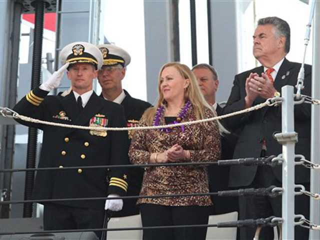 U.S. Navy Commander Thomas Shultz, USS Michael Murphy commanding officer, left, Maureen Murphy, mother of Navy SEAL Lt. Michael P. Murphy, foreground center,  take part in the commissioning ceremony for the Navy's newest guided-missile destroyer, the USS Michael Murphy, Saturday in New York.