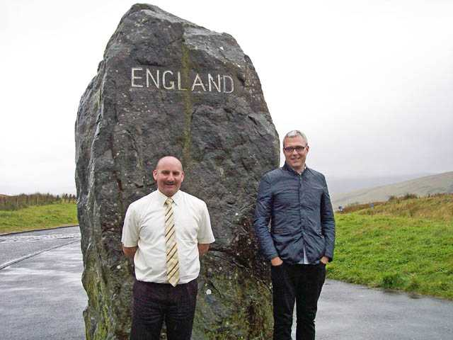 "Left to right, coach driver Paul Jacques and tour director Matt Bauer at the border of England and Scotland. This is the view looking into England. The opposite side of the stone reads ""Scotland."""