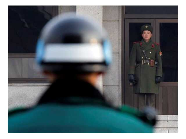 In this 2011 file photo, a North, right, and a South Korean soldier look at each other's sides at the Panmunjom (DMZ) that separates the two Koreas. A North Korean soldier killed two of his superiors Saturday and defected across the border.