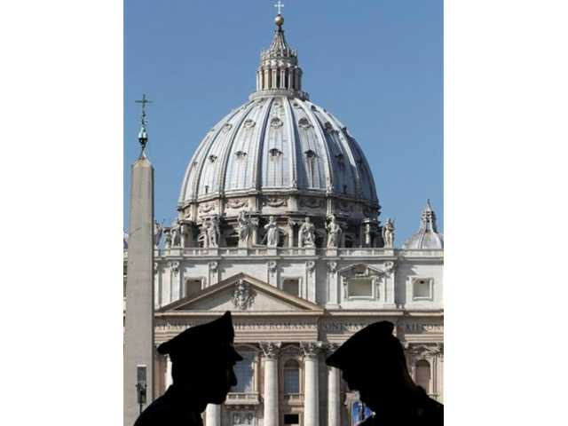 Italian police officers are silhouetted in front of the Vatican, Saturday, Oct. 6, 2012. The verdict in the case of the pope's butler accused of leaking papal documents is expected Saturday Oct. 6, 2012, and may help close one of the most damaging scandals of Pope Benedict XVI's papacy.