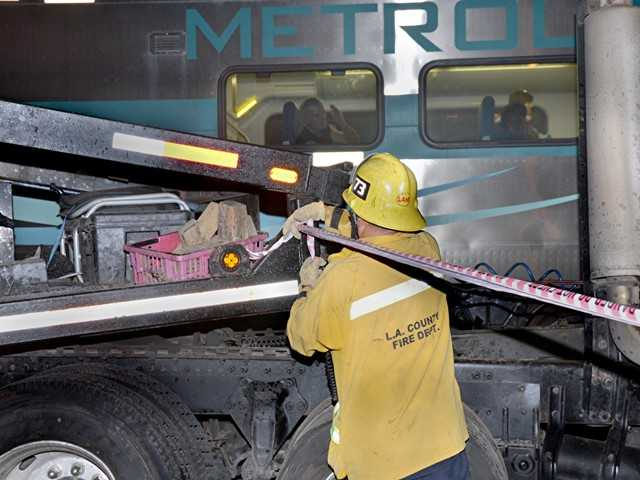 Los Angeles County firefighter Larry Hoerner stretches caution tape as a passenger on the Metrolink train waves following a train vs. big rig crash in Newhall. Photo by Rick McClure