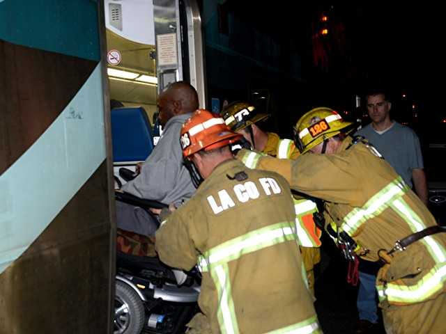 Firefighters assist a handicapped passenger from the Metrolink train that collided with a tractor-trailer rig in Newhall on Saturday night. Photo by Rick McClure