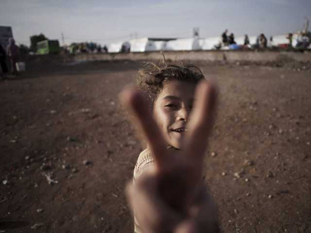 A Syrian girl, who fled her home with her family due to fighting between government forces and rebels, flashes the victory sign.