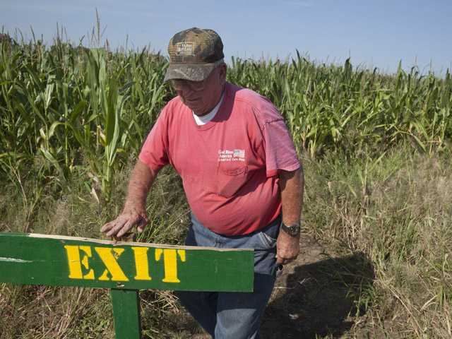In this photo taken Tuesday, Bob Schaefers checks a sign at his corn maze near Mayflower, Ark.