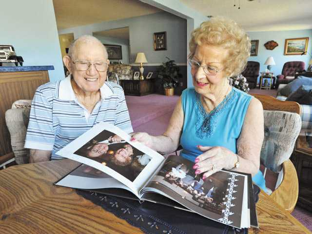Jerry, left, and Evelyn Martin look through a photo album from Evelyn's 85th birthday celebration in their Friendly Valley home.
