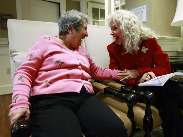Alexis McKenzie, right, executive director of an Alzheimer's assisted-living facility, laughs with resident Catherine Peake in the District of Columbia.