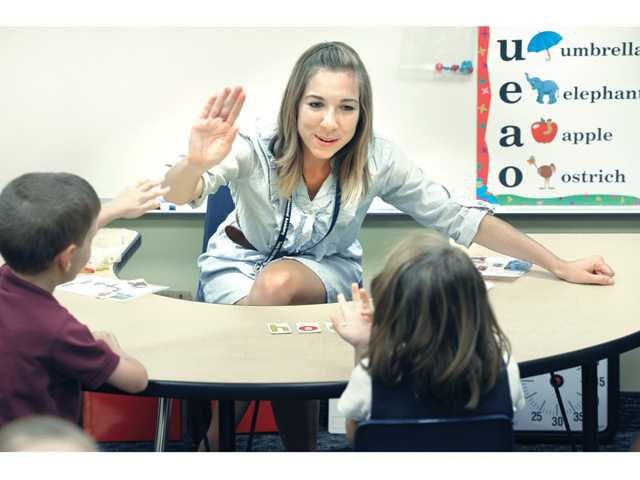 Teacher Katarina Montano high fives Imago Dei School students with developmental or learning disabilities while working on a lesson at Trinity Classical Academy on Thursday.