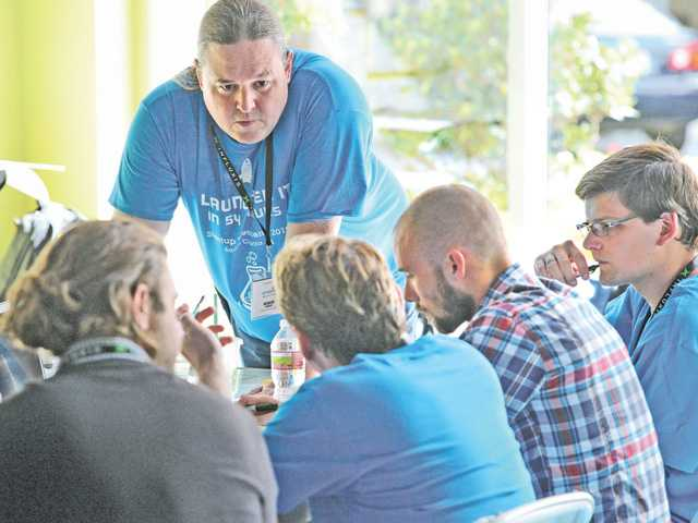 Brian Ragazzi, standing, works with the Zejoop group as it works on a startup company for event planning at the SCV Startup Weekend held in Valencia on Saturday.