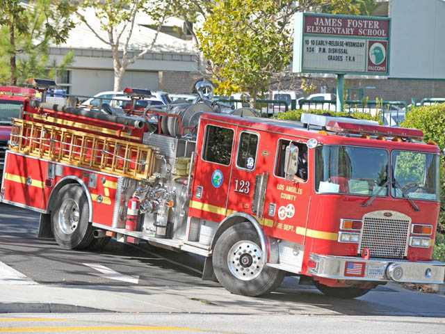 Firefighters leave after dousing a small fire in a rooftop air conditioner at James Foster Elementary School in Saugus on Tuesday morning.