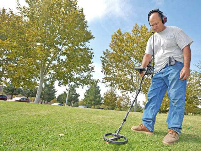 Doug Ingle sweeps around the grass with his metal detector at Central Park in Saugus on Tuesday.