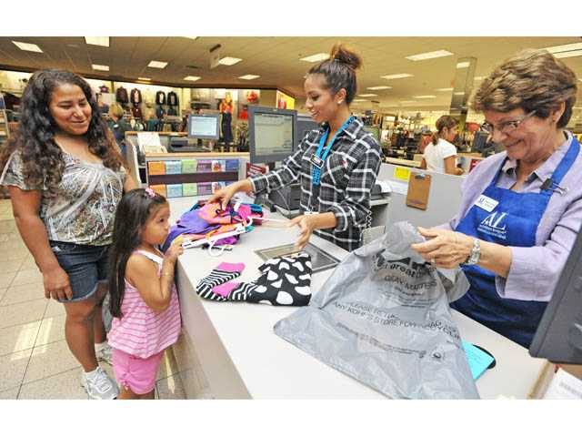 Sales associate Noel Grob, center, and Assistance League volunteer Mary Ann Germek, right, help ring up clothes for Sonia Lopez, 5, after she and her mother Sonia Estrada shop at Kohl's in Valencia on Tuesday.
