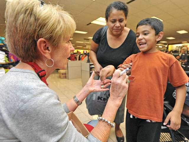 Moises Perez, 7, smiles as he receives a $20 gift card for Payless Shoes from Assistance League volunteer Betty Rabinfung, left, after shopping with his mother Maria Perez at Kohl's in Valencia on Tuesday.