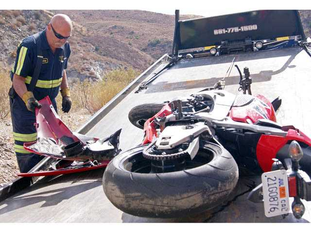 A driver with Preferred Towing loads a motorcycle involved in a crash on San Francisquito Canyon Road on Wednesday.