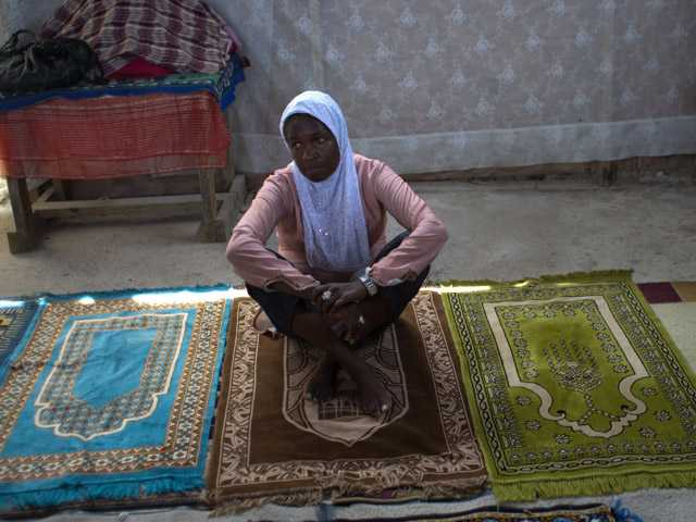 Darlene Derosier, 43, sits on a prayer rug at the Al-Fattah Mosque in Gressier, Haiti. Islam has won a growing number of followers in this impoverished country.