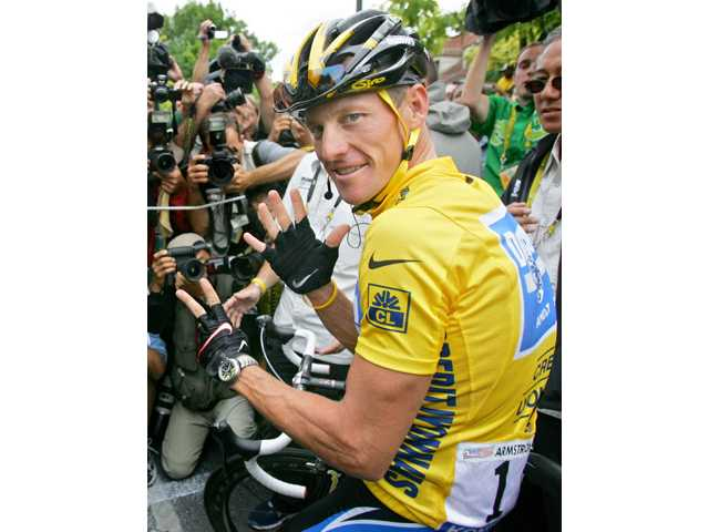 Lance Armstrong surrounded by press photographers, signaling seven, for his seventh straight win in the Tour de France cycling race in 2005.