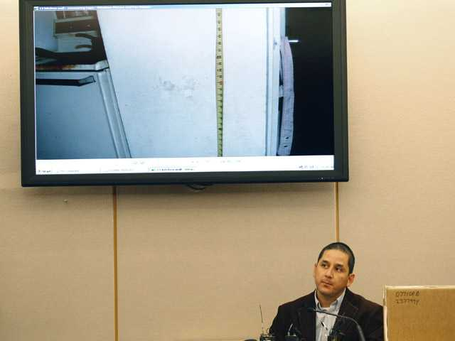 Dallas police officer Abel Lopez in front of a display showing a crime scene photo of little hand prints on a wall while testifying about his investigation.