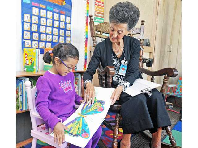 First-grader Vanessa Rodriguez, 5, and Read With Me volunteer Lynn Stegen read at Newhall Elementary on Wednesday.