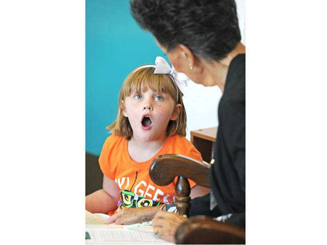 "Talia Einaudi, 6, reacts as she reads ""Dinosaur Days with Read With Me volunteer Lynn Stegen at Newhall Elementary School on Wednesday."