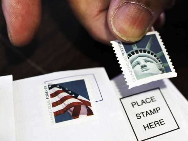 In this Dec. 5, 2011, photo, a customer places first class stamps on envelopes at a U.S. Post Office in San Jose, Calif. It'll cost another penny to mail a letter in 2013.