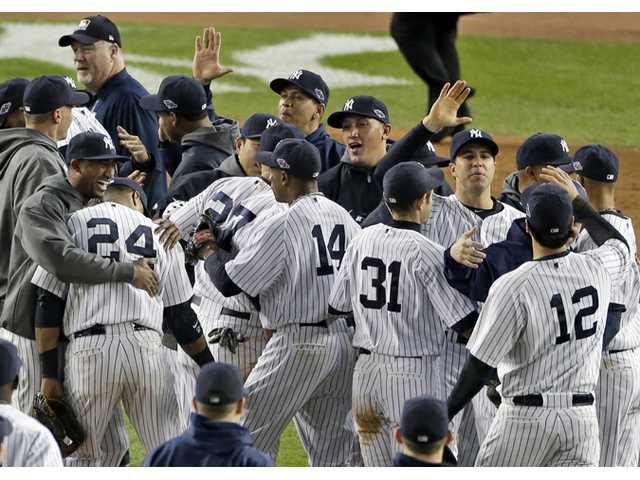The New York Yankees celebrate after winning the American League division baseball series after beating the Baltimore Orioles 3-1 in Game 5 on Friday in New York.