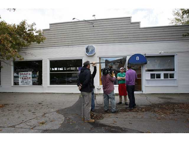 A pizzeria worker is interviewed in front of the former fitness studio where prostitution has been alledged to have occured in Kennebunk, Maine.