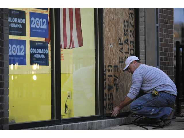 Jason Payseno, 39, replaces a window shot out at the Obama for America headquarters in Denver.