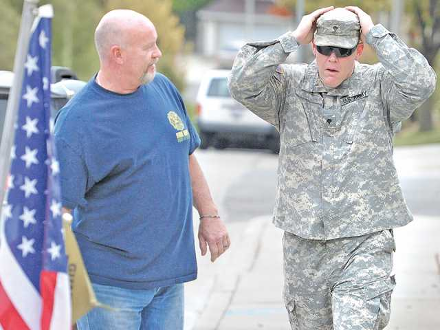 A U.S. Army specialist, right, reacts to the small group of well-wishers gathered in front of the home of Dave Myers, left, in Saugus at a send-off for the soldier on Friday.