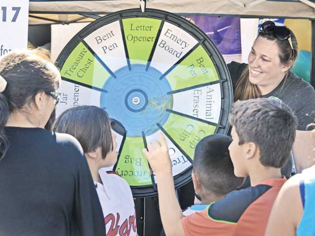 Chiropractic assistant Corinne Knox, right, chats with attendees as they spin for prizes at the Back to Health display booth.