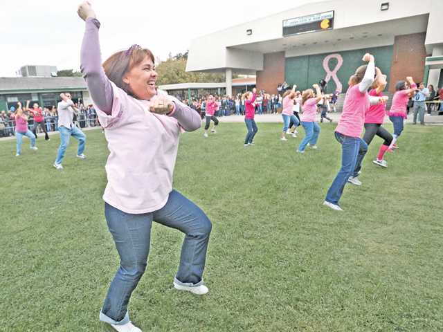 Laura Shay dances with teachers and administrators during a flash mob event at Sierra Vista Junior High in Canyon Country on Friday. The dance was not just a treat for students, but also in honor of Breast Cancer Awareness Month.